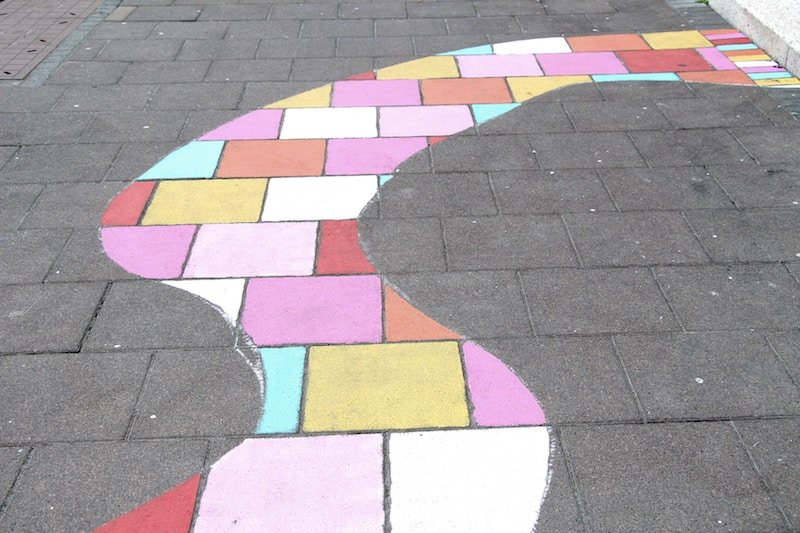 Brown brick path, with colorful winding path painted over the bricks.