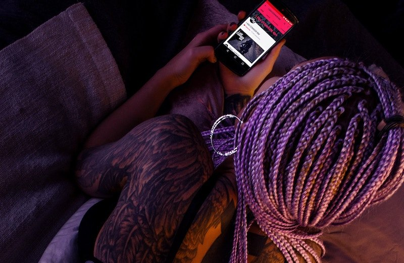 Girl with braids, sitting in dark room lit with red while looking at cell phone.