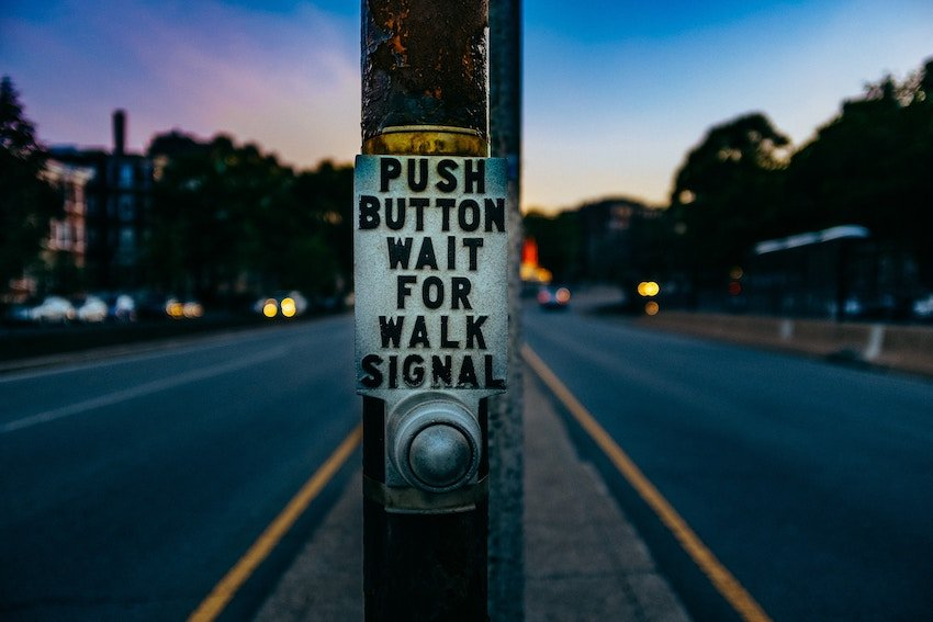 crosswalk sign that says press button for walk signal