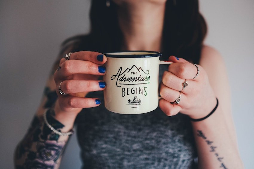 woman holding mug that reads the adventure begins