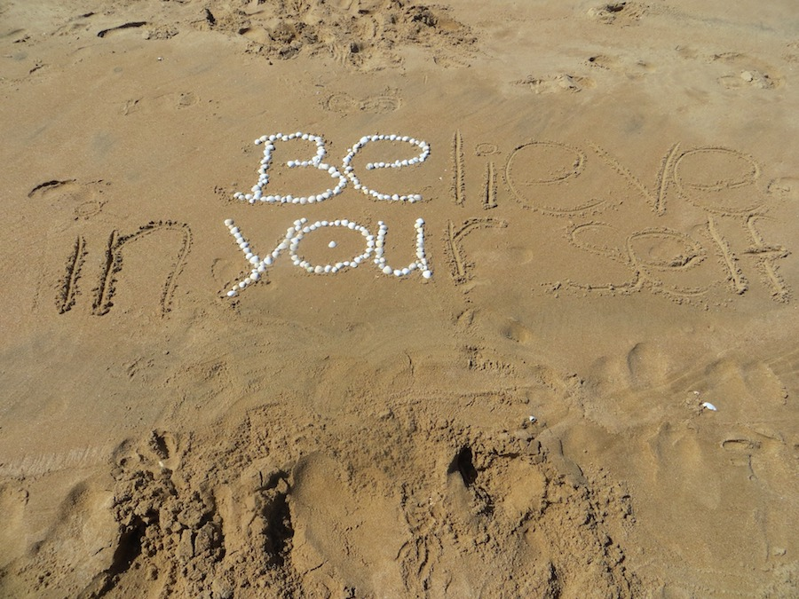 sand with message written in stones
