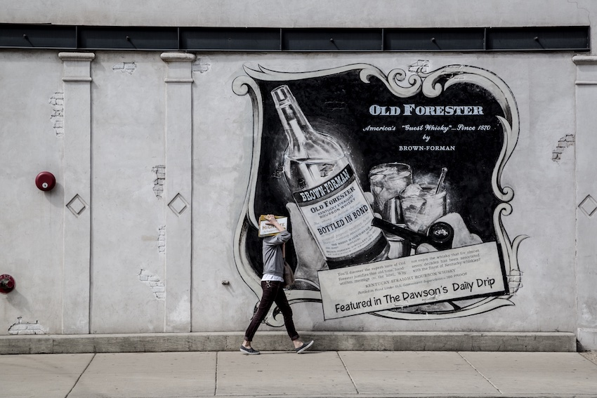 man walking by old advertisement