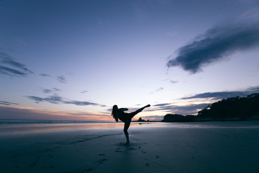 girl doing a roundhouse kick on the beach