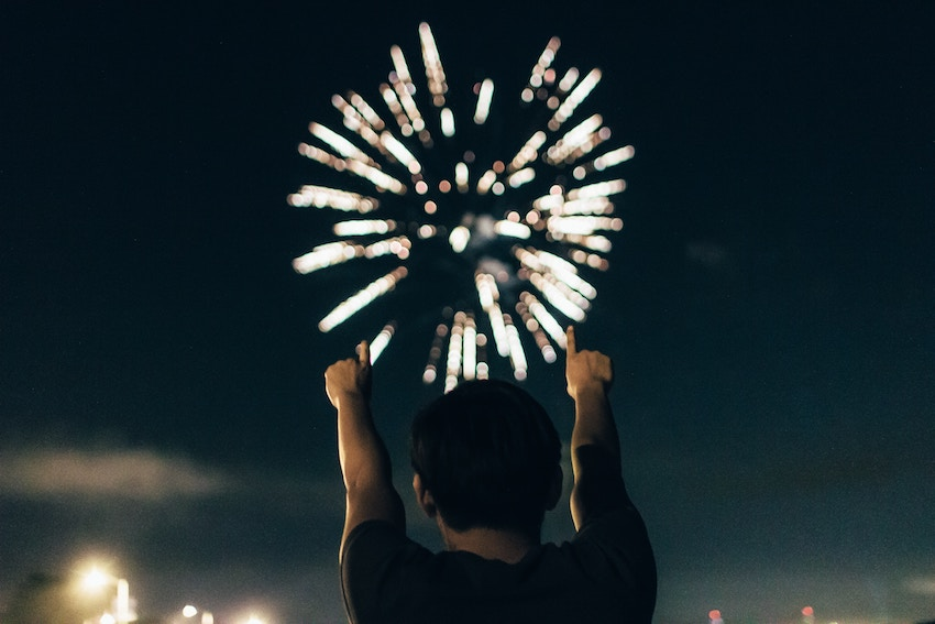 man pointing at fireworks