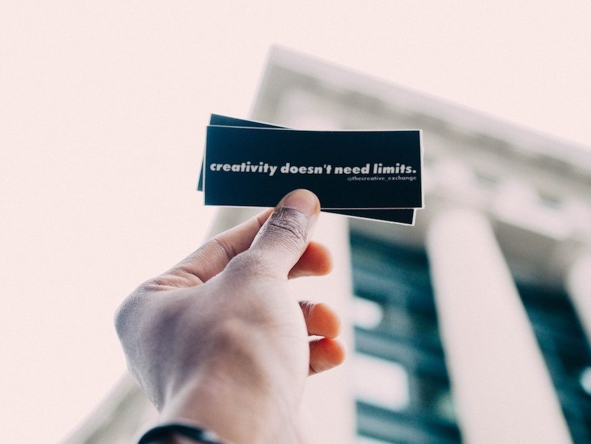 man holding note that says creativity doesnt need limits