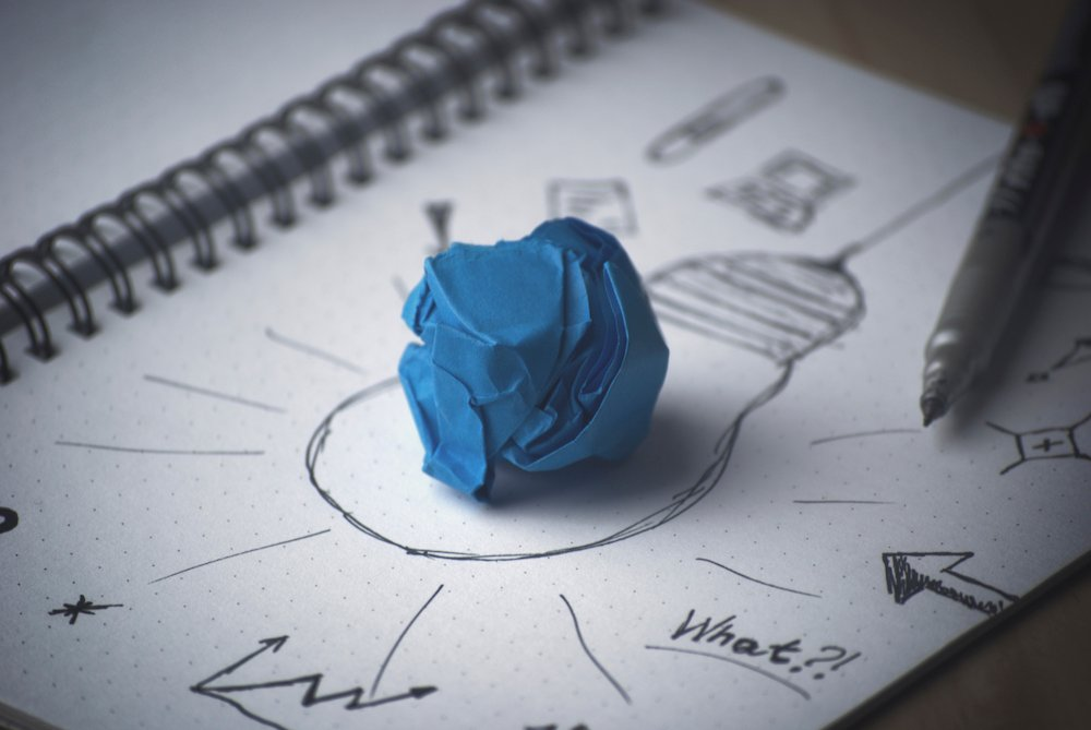 paper with notes and lightbulb drawn on with crumpled paper on top
