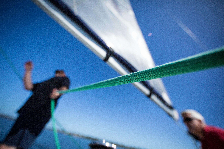 man pulling green rope on sailboat