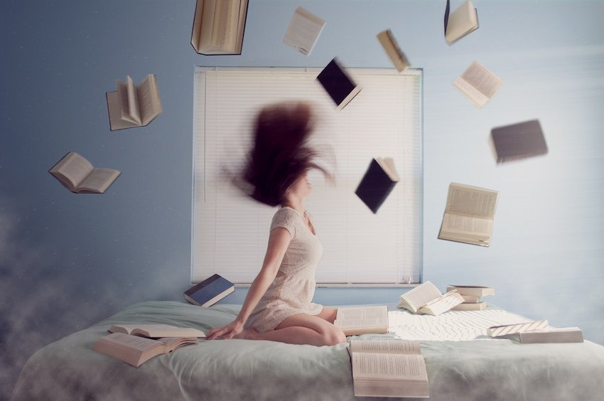 woman on bed with books flying around