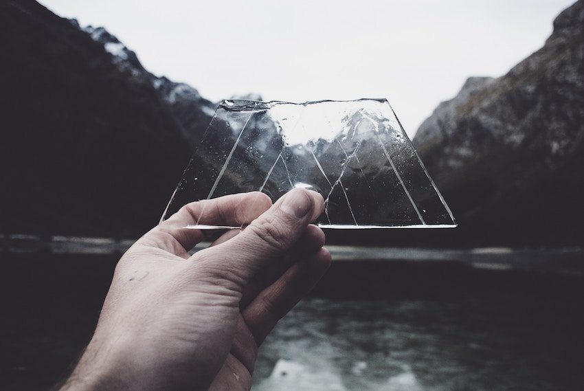 piece of ice held up over mountain